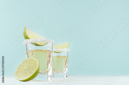 Photo Alcohol cocktail - tequila with salty rim, piece lime in shot glasses in modern elegant pastel blue interior, copy space