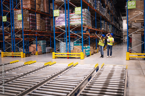 Warehouse workers checking inventory and goods distribution in large storehouse Fototapet
