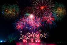 Amazing Beautiful Colorful Fireworks Display On Celebration Night, Showing On The Sea Beach With Multi Color Of Reflection On Water