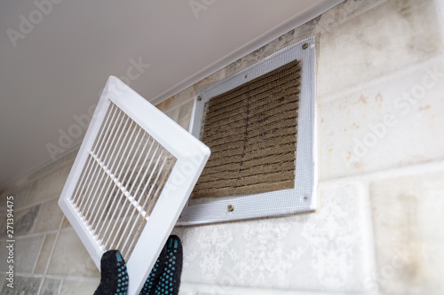 Fotografia, Obraz  repair service man removing a dirty air filter on a house so he can replace it with a new clean
