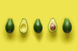 Leinwandbild Motiv Row of fresh wholes and halves of organic avocado with kernels in center on yellow backgrond. Top view