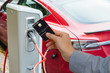 A man pays for charging an electric car.