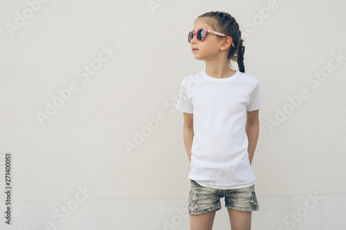 Fototapeta  Kid girl wearing white t-shirt with space for your logo or design in casual urba