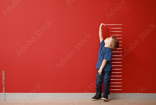 Fotografía Little boy measuring height near color wall