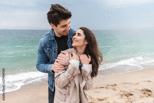 Leinwand Poster Happy young couple wearing autumn coats