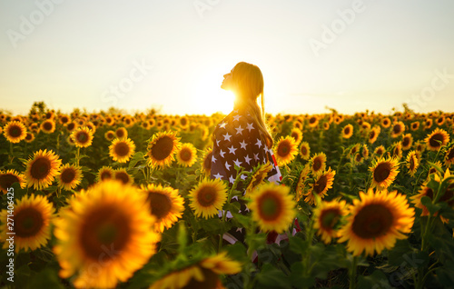 Tuinposter Zonnebloem Beautiful girl with the American flag in a sunflower field. 4th of July. Fourth of July. Freedom. Sunset light The girl smiles. Beautiful sunset. Independence Day. Patriotic holiday.