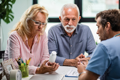 Senior couple getting prescription medicine from their doctor during medical appointment Canvas Print