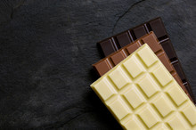 Slabs Of White, Milk And Dark Chocolate On Top Of Each Other On A Black Slate From Above. Space For Text.