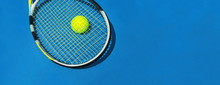 Summer Sport Concept With Tennis Ball And Racket On Blue Hard Tennis Court. Flat Lay, Top View, Copy Space. Blue And Yellow, Banner Size.