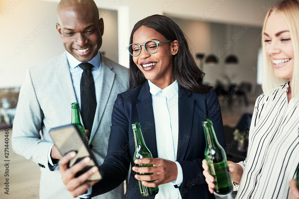 Fototapety, obrazy: Smiling businesswoman showing coworkers photos over drinks after