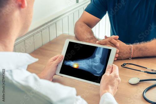 Valokuva  Doctor holding a digital tablet with x-ray of foot of the patient
