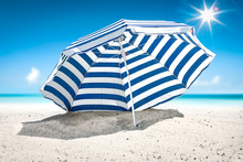 Summer Background Of Umbrella With Free Space For Your Decoration On Hot Sand. Sunny Day And Ocean Landscape.