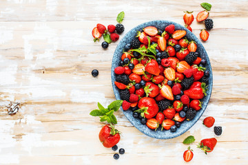 Draufsicht von frischen reifen Erdbeeren, von Blaubeeren und von Brombeeren auf Holztisch mit freiraumraum