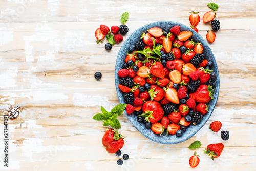 fototapeta na szkło Draufsicht von frischen reifen Erdbeeren, von Blaubeeren und von Brombeeren auf Holztisch mit freiraumraum