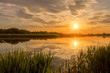Sunset above the pond or lake with cloudy sky at summer and water reflection.