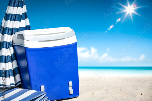 Poster Ecole de Danse beach fridge on sand with umbrella and free space for your decoration. Summer landscape of ocean and blue sky.
