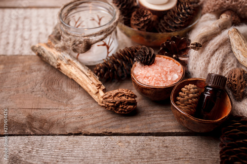Stickers pour portes Spa Wood scents for winter time aromatherapy. Pine cones, candles, essential oil bottles, top view. Spa relax winter concept, copy space