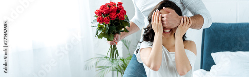 Fototapeta partial view of man with bouquet of red roses closing woman eyes to make surprise in bedroom obraz