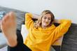 canvas print picture - lächelnde Frau liegt mit geschlossenen Augen entspannt auf dem Sofa