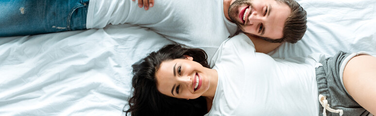 top view of happy couple lying together in bed, panoramic shot