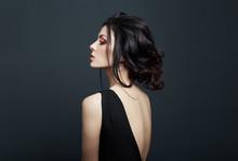 Brunette Woman Smoking On Dark Background In Black Dress. Erotic Girl