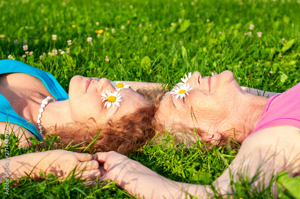 Fototapety, obrazy: Happy old mother with an adult daughter lie on a glade putting white chamomile flowers to her eyes holding hands. Happy relationship of older mom and daughter.