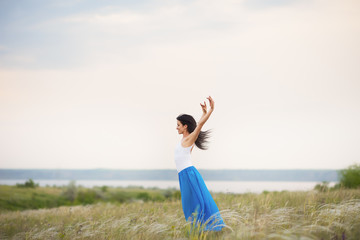 Classical dancer woman. Charming ballerina with windy hair in blue chiffon skirt dancing by the sea background. Sun shines on her. Horizontal.