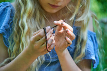 Adorable Child Blond Girl Holding A Earthworm In The Garden. Selective Focus