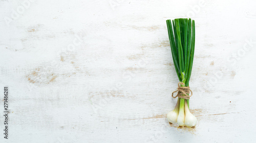 Fototapeta Green onion on a white wooden background. Top view. Free space for text. obraz