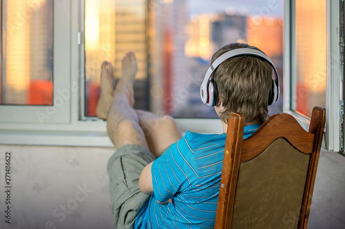 guy boy in headphones are audiophile enjoying life listening to music sitting upside down in big headphones on background of bright rays of the daytime summer sun in city Canvas Print