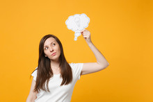 Portrait Of Pensive Young Woman In White Casual Clothes Holding Say Cloud With Lightbulb, Idea Isolated On Bright Yellow Orange Wall Background In Studio. People Lifestyle Concept. Mock Up Copy Space.