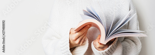Close view of woman in white woolen sweater holding an open book with pink cover in hands. Long wide banner with free space for your mock up of reading book concept background.