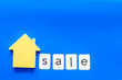 Buy house with house figure and sale copy on office desk blue background top view mock-up
