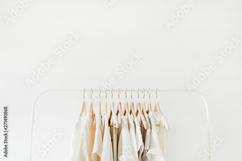 Obraz Minimal fashion clothes concept. Female blouses and t-shirts on hanger on white background. Fashion blog, website, social media hero header template. - fototapety do salonu