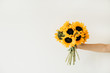 Yellow sunflowers bouquet in female hand on white background. Summer floral concept.