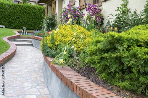 Allée fleurie (ancolie, mufliers, gueule de loup, genet, iris) avec un sol en ma Fotobehang