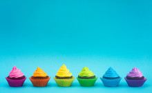 Rainbow Colored Frosted Chocolate Cupcakes On Teal Background