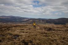 Women In Yellow Rainoat Walking Through The Wicklow Mountains