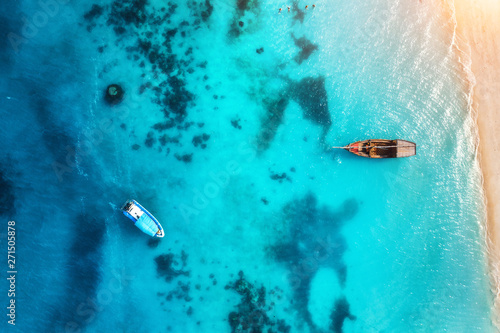 Foto auf Leinwand Turkis Aerial view of the fishing boats in transparent blue water at sunset in summer. Top view from of boat and sandy beach. Indian ocean in Zanzibar, Africa. Landscape with yachts and clear sea. Travel