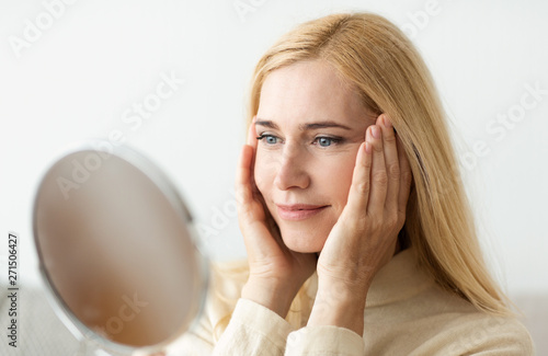 Photo Mature Woman Looking At Mirror And Touching Face