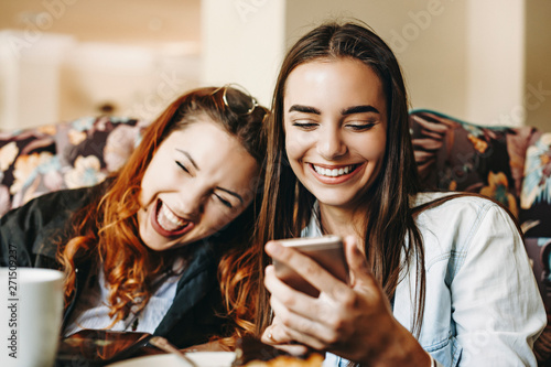 Fotografia Beautiful young female holding a smartphone laughing while showing something to her girlfriends which is laughing leaning head on her shoulder