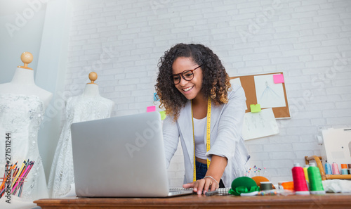 Photo Portrait of beautiful african american black designer woman work with computer in tailer fabric fashion small business workshop office