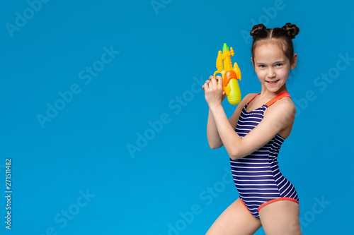 Little girl in swimsuit holding water gun in attack pose