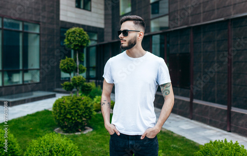 Tablou Canvas A young stylish man with a beard in a white T-shirt and glasses