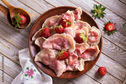 Dumplings, filled with strawberries. Varenyky, vareniki, pierogi, pyrohy - dumplings with filling. View from above, top studio shot