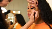 Makeup Artist Draws Arrows On Eyelids Of African Girl. Evening Make-up. Closeup Portrait Side View