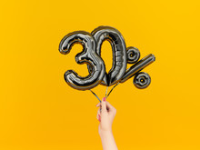 Thirty Percent Symbol Discount. 30 % Sale Banner Black Flying Foil Balloons On Yellow. 3d Rendering.