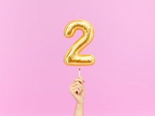 Two Year Birthday. Female Hand Holding Number 2 Foil Balloon. Two-year Anniversary Background. 3d Rendering