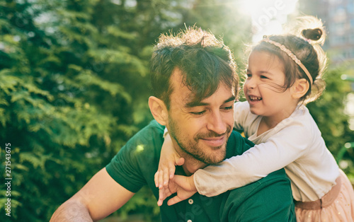 Outdoor image of happy cute little girl smiling and playing with her father. Handsome dad and pretty kid having fun and playing at playground. Daddy and daughter shares love together. Fatherhood - 271543675