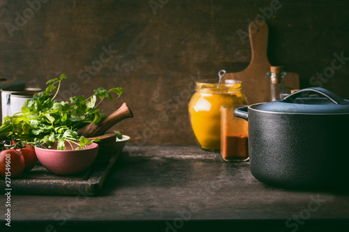 Fotografia Food background with cast iron cooking pot, fresh seasoning and spices on rustic kitchen table